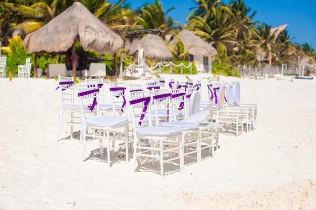 Cadeiras de casamento branco decoradas com arcos roxos na praia Foto Premium