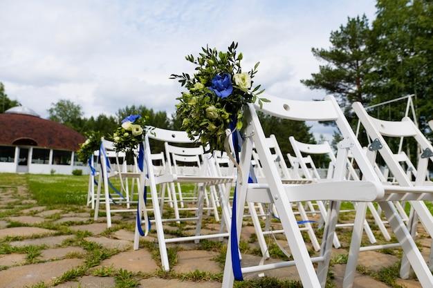 Cadeiras de madeira brancas decoradas com flores e fitas de cetim brilhantes, decoração de casamento na cerimônia na floresta de pinheiros Foto Premium