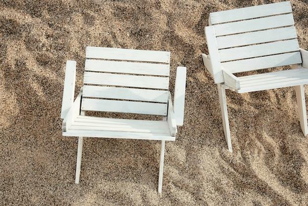 Cadeiras de madeira em uma praia arenosa. Foto Premium
