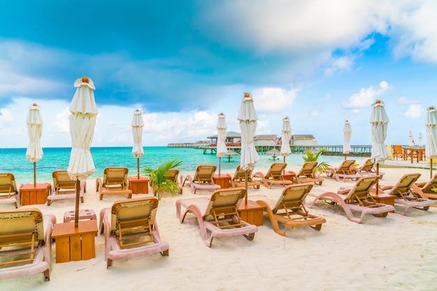 Cadeiras de praia com o guarda-chuva na ilha de maldivas, no sandy beach branco e no mar. Foto Premium