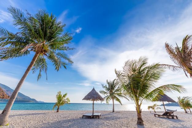 Cadeiras de praia, guarda-chuva e palmas das mãos na bela praia para férias e relaxamento na ilha de koh lipe, tailândia Foto Premium