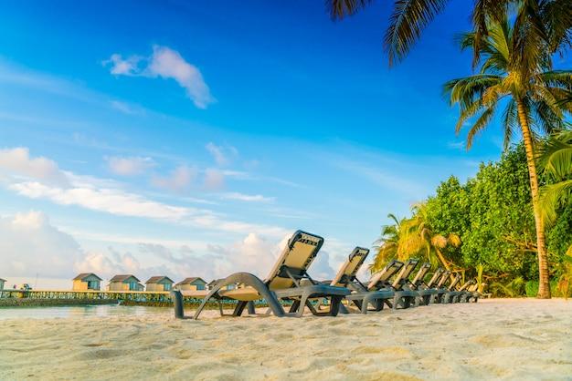 Cadeiras de praia na ilha de maldivas com as casas de campo da água no tempo do nascer do sol. Foto Premium