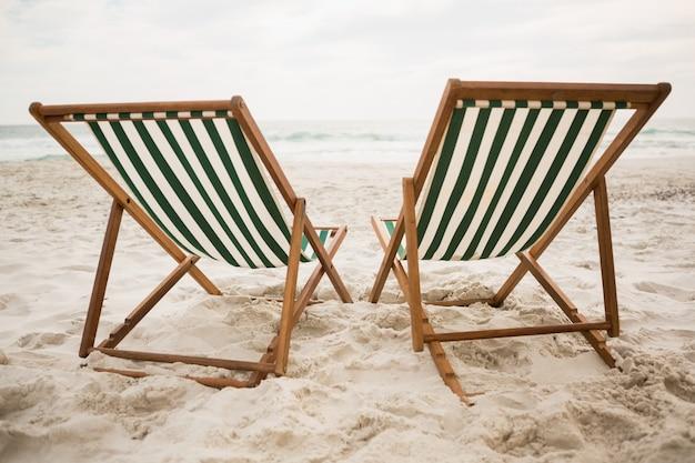 Cadeiras de praia vazias na areia da praia tropical Foto gratuita