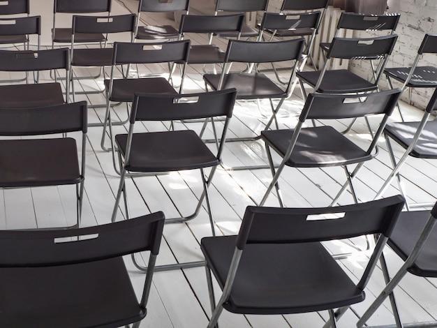 Cadeiras dobráveis pretas ficam em fila na sala de conferências branca Foto Premium
