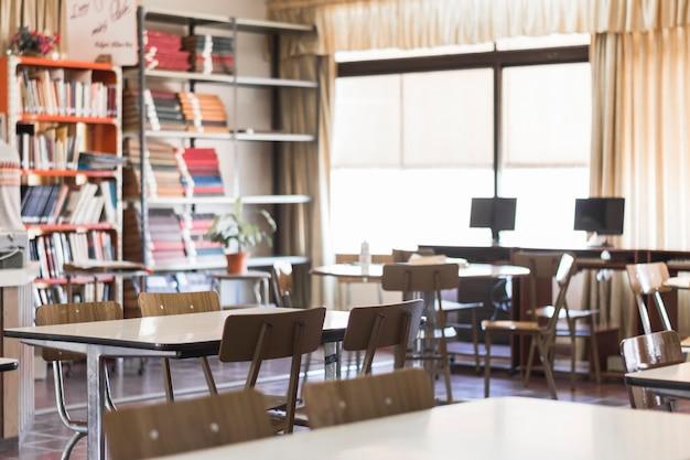 Cadeiras e mesas na sala de aula vazia Foto Premium