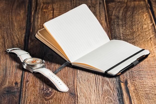 Caderno aberto com caneta e relógio de pulso na mesa Foto Premium