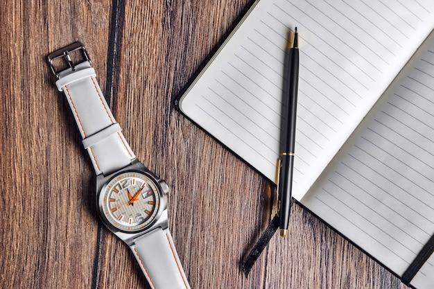 Caderno aberto com caneta e relógio de pulso Foto Premium