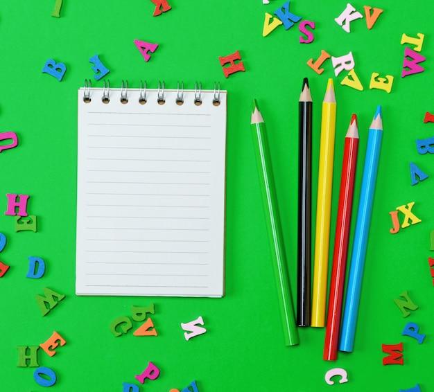 Caderno aberto com folhas brancas em branco na linha, lápis de madeira coloridos Foto Premium