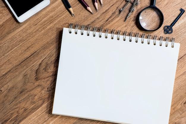 Caderno aberto com folhas brancas em branco na mesa de madeira Foto Premium