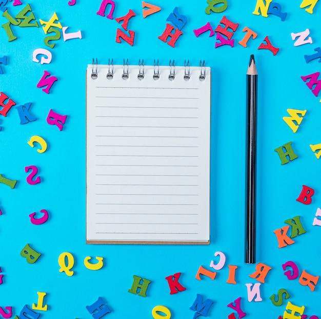 Caderno aberto com folhas brancas vazias e lápis preto Foto Premium