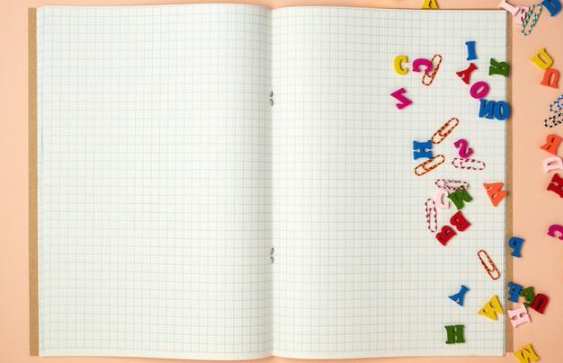 Caderno aberto com lençóis brancos em uma gaiola e pequenas letras de madeira coloridas Foto Premium