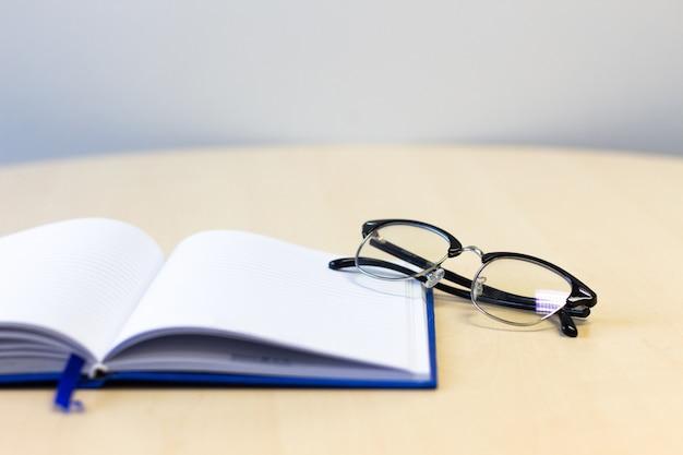 Caderno aberto com óculos na mesa de madeira, cópia espaço para texto. Foto Premium