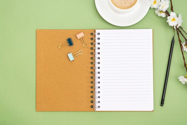 Caderno aberto com uma página vazia e xícara de café. tampo da mesa, espaço de trabalho sobre fundo verde. lay criativo apartamento. Foto Premium