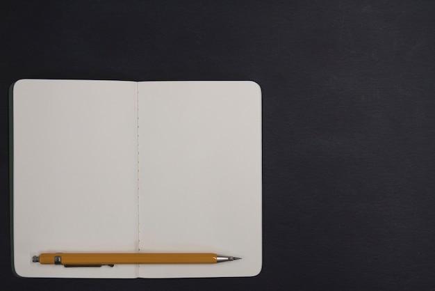 Caderno aberto e lápis sobre fundo preto Foto Premium
