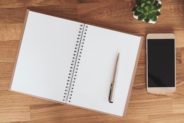 Caderno aberto em branco ao lado de smartphone e xícara de café na mesa de madeira Foto Premium