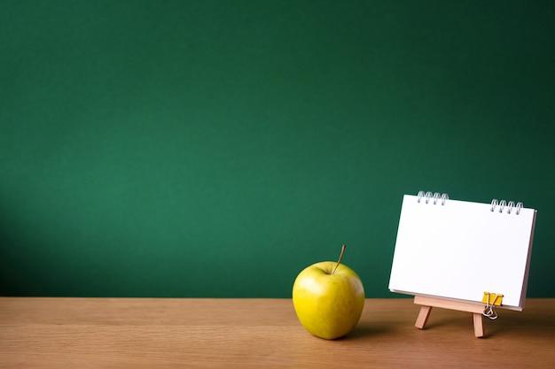 Caderno aberto em cavalete em miniatura e maçã verde Foto Premium