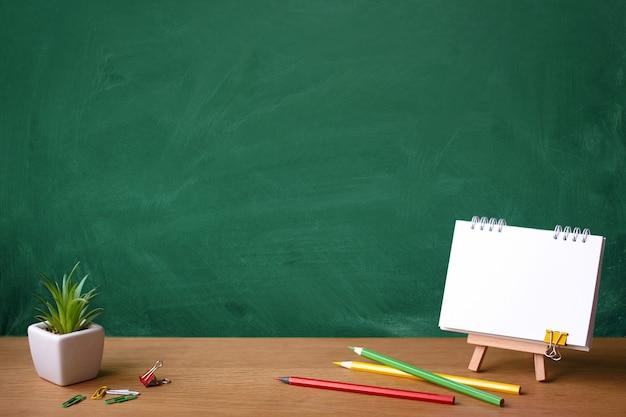 Caderno aberto em cavalete em miniatura, suculenta em uma panela e lápis de cor no fundo de uma lousa verde com manchas de giz, copie o espaço Foto Premium