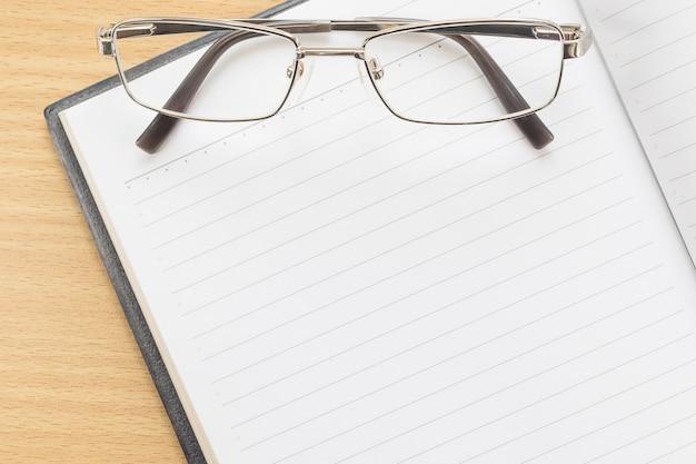 Caderno aberto página em branco e óculos Foto Premium