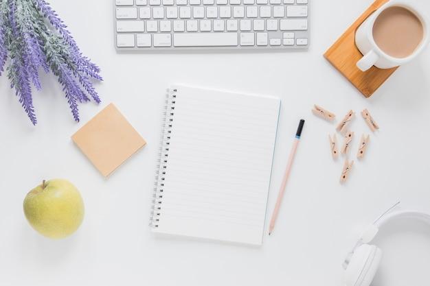 Caderno aberto perto de artigos de papelaria na mesa branca com gadgets e xícara de café Foto gratuita
