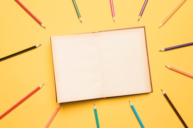 Caderno aberto, rodeado por lápis de cores diferentes Foto gratuita