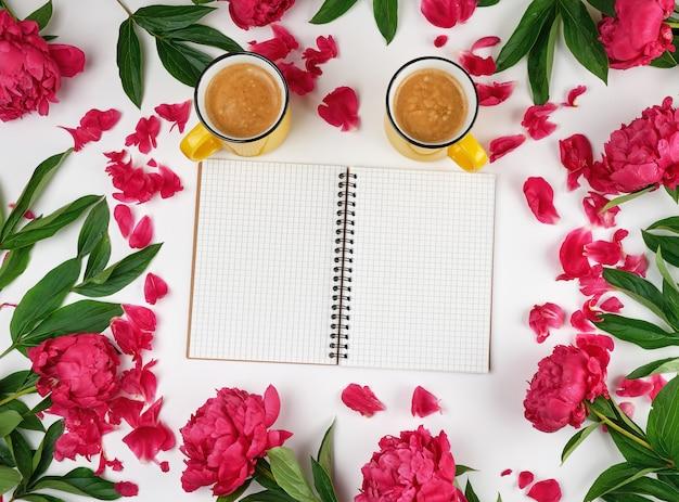 Caderno aberto vazio em uma gaiola e duas xícaras de café amarelas Foto Premium