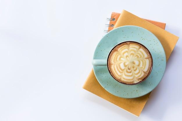 Caderno alaranjado com caderno marrom e café do copo no fundo isolado. Foto Premium