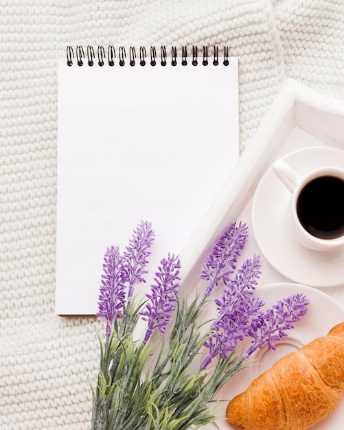 Caderno ao lado da bandeja com café da manhã Foto gratuita