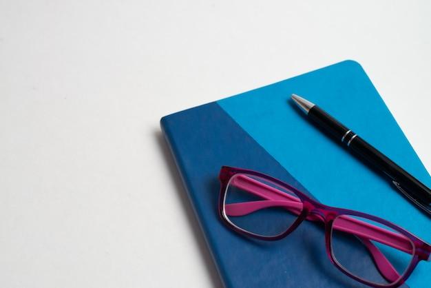 Caderno azul com óculos e caneta preta Foto Premium
