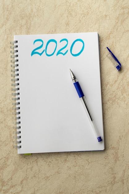 Caderno branco e a inscrição azul 2020. caneta azul em papel e boné em uma tabela Foto Premium