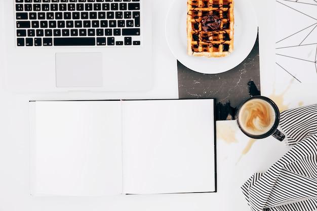 Caderno branco em branco; computador portátil; waffle; xícara de café e toalha de mesa no fundo branco Foto gratuita
