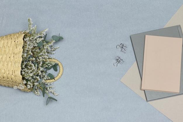Caderno cinza e clipes de papel, nota e papel rosa, cesto de palha com flores brancas e ramos de eucalipto Foto Premium