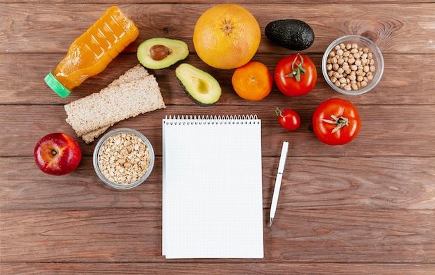 Caderno com caneta e legumes Foto gratuita