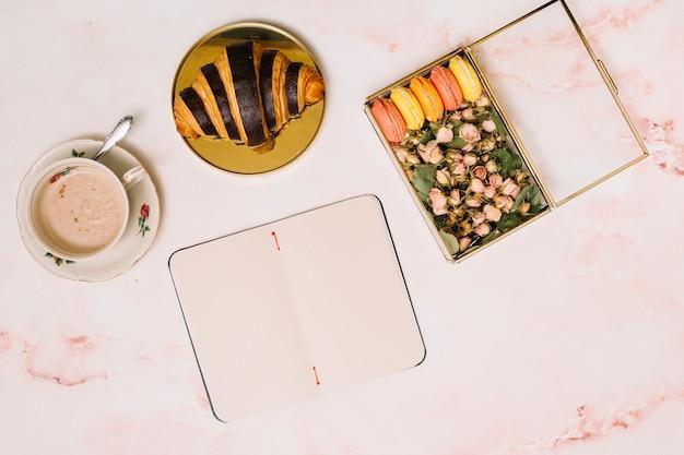 Caderno com croissant e caixa com flores na mesa Foto gratuita