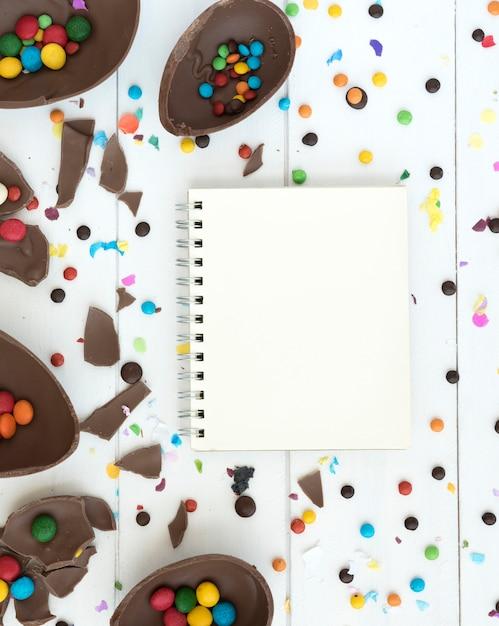 Caderno com ovos de páscoa de chocolate aberto e doces Foto gratuita