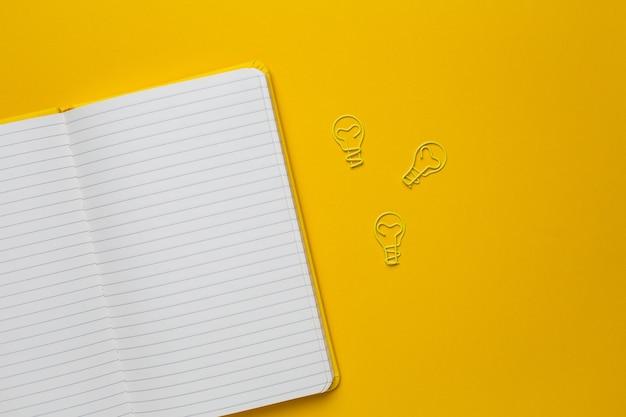 Caderno com páginas em branco e paperclip lâmpada idéia em amarelo Foto Premium