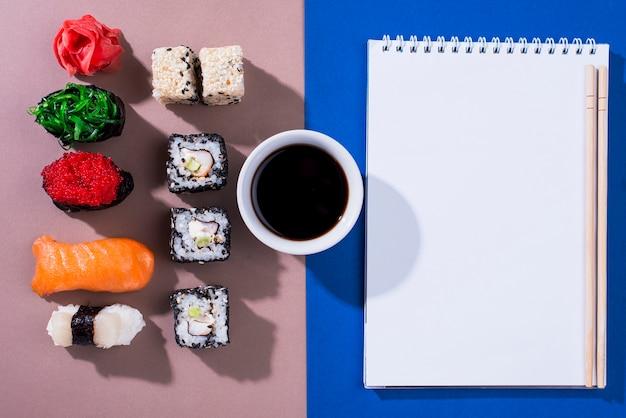 Caderno com rolos de sushi ao lado Foto gratuita
