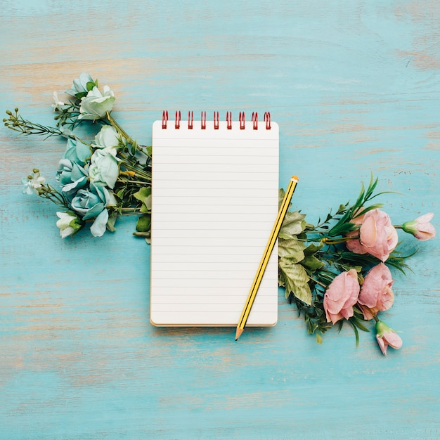 Caderno da escola com espaço e flores da cópia. Foto gratuita