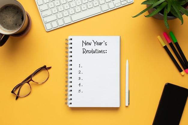 Caderno de 2020 ano novo com lista de resoluções e objetos em fundo amarelo Foto Premium