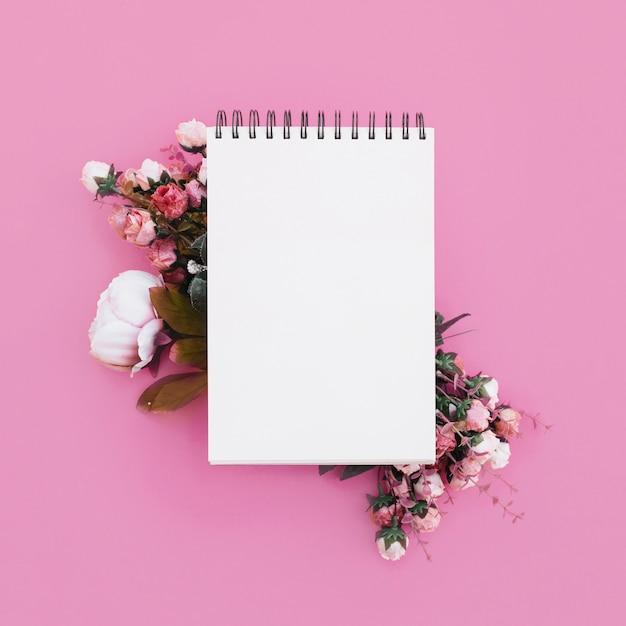 Caderno de casamento com lindas flores em fundo rosa Foto gratuita