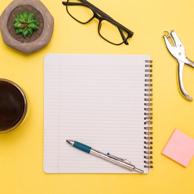 Caderno de configuração plana com caneta no espaço de trabalho criativo Foto gratuita
