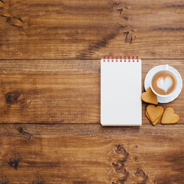 Caderno de escola e caneca de café em um fundo de madeira Foto gratuita
