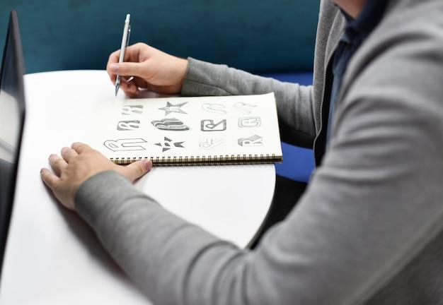 Caderno de exploração de mão com drew brand logo design criativo idéias Foto gratuita