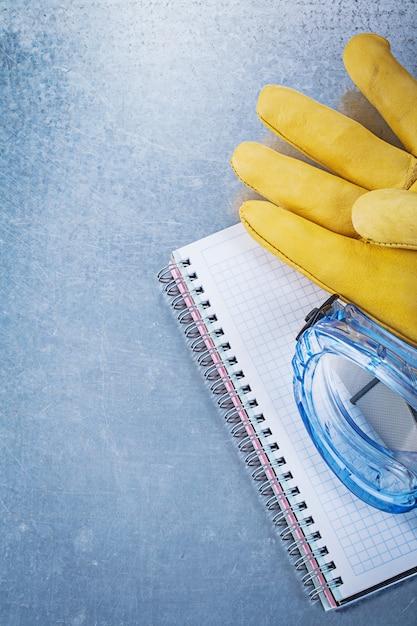 Caderno de luvas de óculos de segurança na mesa metálica, conceito de construção Foto Premium