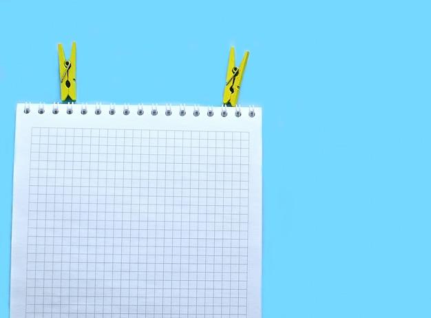 Caderno de papel branco sobre um fundo azul e dois prendedores de roupa amarelas Foto Premium