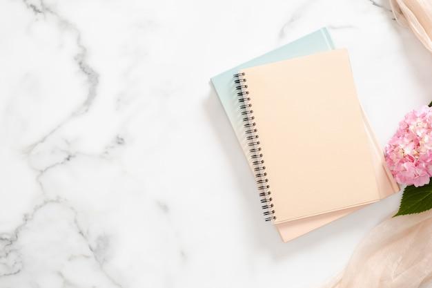 Caderno de papel em branco, flor de hortênsia rosa, fundo cobertor pastel Foto Premium
