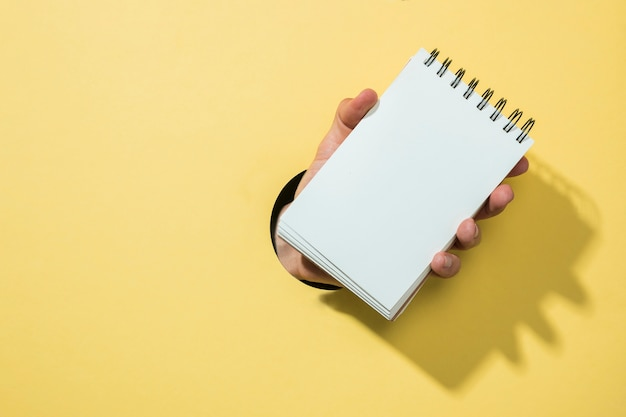 Caderno de vista frontal com fundo amarelo Foto gratuita