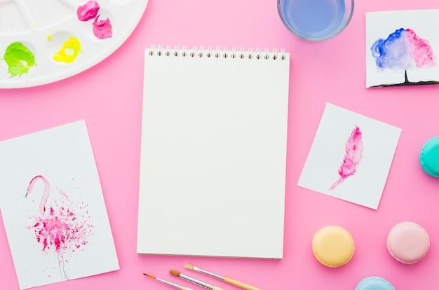 Caderno de vista superior com aquarela e macarons Foto gratuita