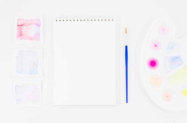Caderno de vista superior com aquarela e pincel Foto gratuita
