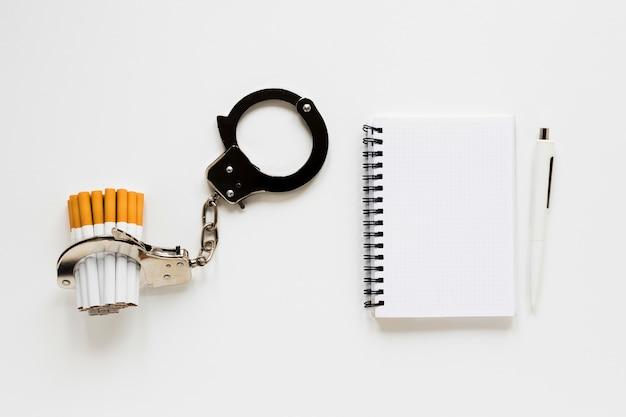 Caderno de vista superior com cigarro e algemas Foto gratuita