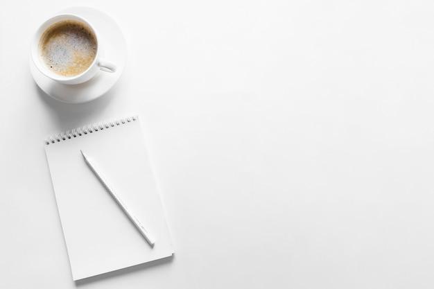 Caderno de vista superior e café em fundo branco Foto gratuita